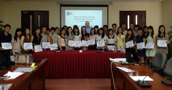 Course participants hold up their certificates